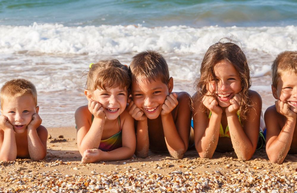 Five smiling kids enjoying on the beach